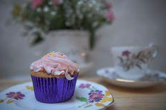 Food photography with homemade cupcake with butter cream topping and floral background. An old fashioned English image with home made vanilla cup cake with a Stock Photo