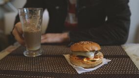 Food photography. Hot cappuccino with hamburger at the table in fast food cafe. Cheeseburger and coffee on the table