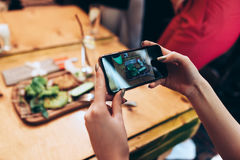 Food photography for social networks. Close-up image of female hands holding phone with food on screen taking picture of Royalty Free Stock Images