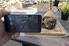 Food photography of tasty black burger in outdoors cafe. Man han. Ds taking food photo by mobile phone Stock Image