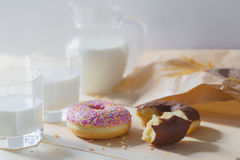 Food photos with milk and donuts. Food photos with milk in a transparent glass jug and three glasses and donuts with chocolate icing and pink with colored powder royalty free stock photos