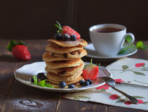 Food photos with pancakes. With blueberries and strawberries with honey sauce, on a white vintage plate with mint leaf stock photo