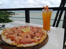 The food pizza and orange juice lunch on a white table with beautiful sea landscape Royalty Free Stock Images