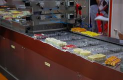 Food plastic packaging machine. Packing food sausage and ham in production line Stock Images