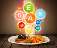 Food plate with delicious meal and healthy vitamin symbols Royalty Free Stock Image