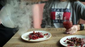 Food plate dish gourmet tartare steam smoke cap dome.the waiter opens the dish with steam in front of the visitor. woman. With a glass of wine at a gourmet stock video