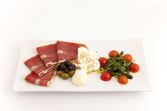 Food plate with ham,olives,cheese,cherry tomatoes and arugula Stock Image