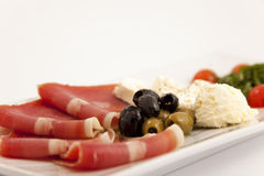 Food plate with ham,olives,cheese,cherry tomatoes and arugula Royalty Free Stock Images