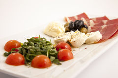 Food plate with ham,olives,cheese,cherry tomatoes and arugula Royalty Free Stock Photography