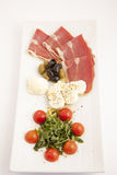 Food plate with ham,olives,cheese,cherry tomatoes and arugula Royalty Free Stock Photos