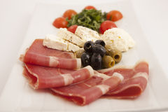 Food plate with ham,olives,cheese,cherry tomatoes and arugula Royalty Free Stock Photo