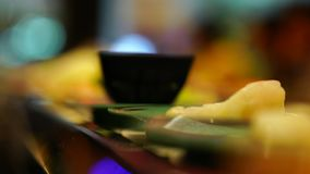 Food in plate rotate on belt movement on bokeh background in the restaurant. Buffet food in Japanese style. Machine for food stock video footage