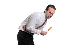 Food Poisoning. A young man suffering from food poisoning from eating a bad corn dog, isolated against a white background Royalty Free Stock Photos