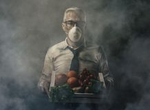 Food pollution and contamination. Businessman with protective mask holding a crate with polluted poisonus vegetables, food pollution concept stock images