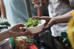 Hands of the poor receive food from the donor`s share. poverty concept. Food for the poor and homeless Help concept royalty free stock photography