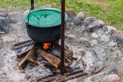 Food pot hangs over burning fire. royalty free stock image