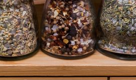 Food preparation concept; close-up image of spice bottles on a light wood rack Royalty Free Stock Photos