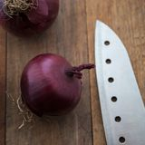 Food preparation, cooking concept: fresh raw red onions, knife on a rustic wooden cutting board background Stock Photos