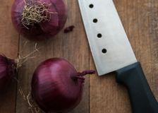 Food preparation, cooking concept: fresh raw red onions, knife on a rustic wooden cutting board background Stock Images
