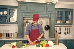 Food preparation, cooking. Man chef cook with knife in kitchen, cuisine. Vegetarian, health, diet, vitamin. Vegetables and tools on table ready for cooking stock photo