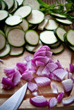 Food preparation: courgettes and onions. Food preparation: chopping up courgettes and onions for a salad with courgettes, lime and mint Stock Image