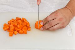 Food preparation - cutting the carrott with knife on the white b Stock Images