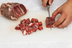 Food preparation - cutting raw meat. With knife stock image