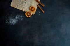 Food preparation. Old recipe and some ingredients. Food preparation. Old recipe and some ingredients (cinnamon sticks, dried orange slices, flour) on dark Stock Image
