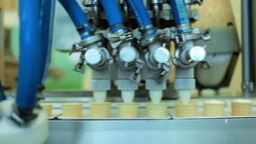 Food processing equipment. Waffle cones filling with ice cream. Production line stock video