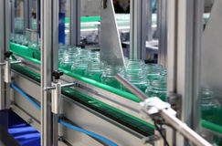 The food-processing industry. The automatic transfer line of packaging of products in banks Royalty Free Stock Photography