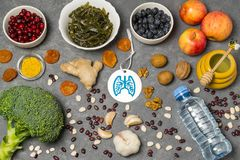 Food products useful for lungs. Set of natural food products are sources of vitamins and minerals. Tag with homemade application from paper - symbol of lungs stock photos