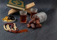 Food Ramadan Sweets mixed of dried fruits and nuts Glass Tea with  rosary and the Quran on the table,  Concept: month fasting cult