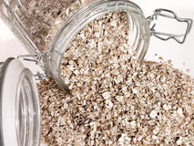 Food: Raw Oats Spilling Out of Glass Jar royalty free stock photography