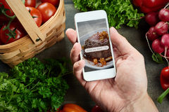 Food recipes on smart phone. Food recipes smart phone on rustic wooden table royalty free stock photos