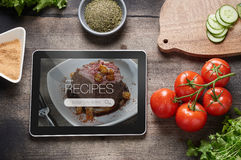 Food recipes on tablet computer. Food recipes tablet computer on rustic wooden table Stock Image