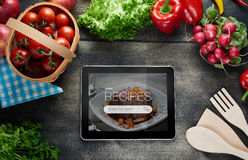 Food recipes on tablet computer. Food recipes tablet computer on rustic wooden table Stock Photo