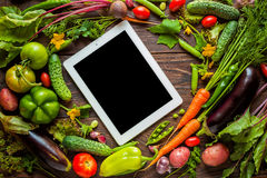 Food recipes tablet computer on rustic wooden table. Black display for text Royalty Free Stock Image