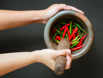 Red and green pepper in mortar Stock Photos