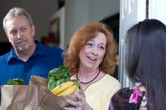 Food Relief Charity. Woman delivers bags of food to the home of a down on their luck couple who have been laid off from their jobs stock photo
