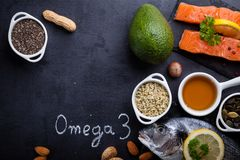 Food rich in vitamin D and omega 3. Black slate table with product rich in omega 3 and vitamin D. Written word omega 3 by white chalk stock images