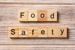 Food safety word written on wood block. Food safety text on table, concept.  Stock Photos