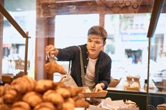 Food, sale, consumerism and people concept -  handsome man with. Tray at bakery store buying buns or pies Stock Photography