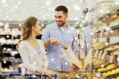 Happy couple with shopping cart at grocery store Royalty Free Stock Images