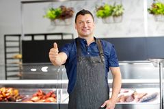 Seafood seller at fish shop showing thumbs up. Food sale, small business and people concept - male seafood seller at fish shop showing thumbs up Royalty Free Stock Images