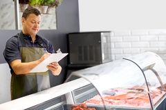 Seller with clipboard selling seafood at fish shop. Food sale, small business and people concept - male seller with clipboard selling seafood at fish shop Royalty Free Stock Images