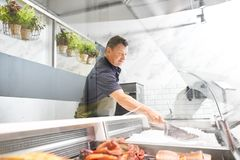 Male seller adding ice to fridge at fish shop. Food sale, small business and people concept - male seller with scoop adding ice to fridge at fish shop Stock Photography