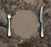 Food Sanitation. Concept and global poverty symbol as a wet ground with a mud puddle of dirty water shaped as a dinner plate with a silver fork and knife as a Stock Image