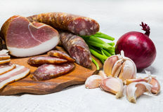Food, sausage, meat. Meat still life with sausage, ham and bacon. vegetables onion, garlic Royalty Free Stock Image