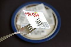 Food savings. Closeup of coupon, fork, and plate Royalty Free Stock Photography