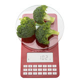 Food scales and green fresh broccoli. On a white background Royalty Free Stock Images